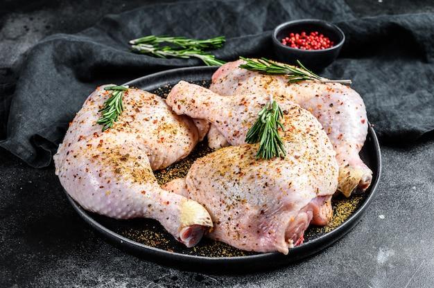Frische rohe hähnchenschenkel, beine auf einem schneidebrett mit gewürzen, kochen. schwarze oberfläche. draufsicht