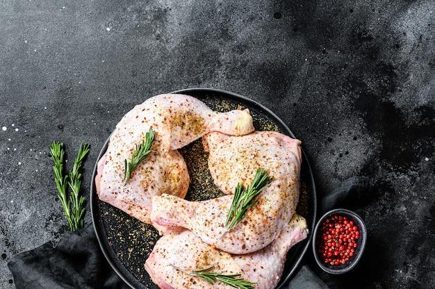 Frische rohe hähnchenschenkel, beine auf einem schneidebrett mit gewürzen, kochen. schwarzer hintergrund