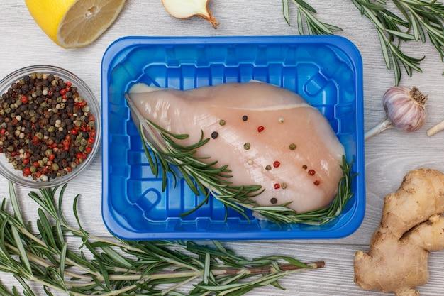 Frische rohe hühnerbrust oder filet in plastikbehälter mit ingwerwurzel, knoblauch, zwiebel, zitrone, pimentpfeffer in glasschüssel und rosmarin auf holzhintergrund. ansicht von oben.