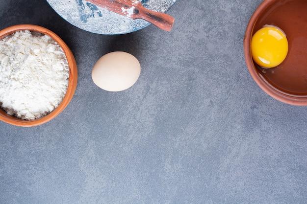Frische rohe hühnereier mit mehl auf steintisch gelegt.