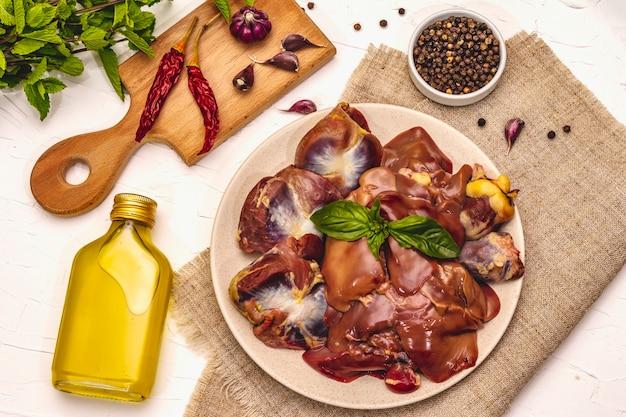 Frische rohe hühnernebenerzeugnisse: herz, leber, magen mit trockenen gewürzen, meersalz, chili, olivenöl, frische minze auf weißem kitthintergrund