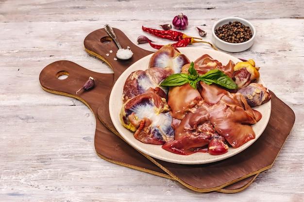 Frische rohe hühnernebenerzeugnisse: herz, leber, magen mit trockenen gewürzen, meersalz, chili-pfeffer auf holztisch