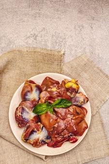 Frische rohe hühnernebenerzeugnisse: herz, leber, magen mit trockenen gewürzen, meersalz, chili-pfeffer auf steinhintergrund