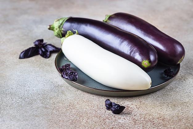 Frische rohe lila und weiße auberginen auf einem keramikteller mit lila basilikum