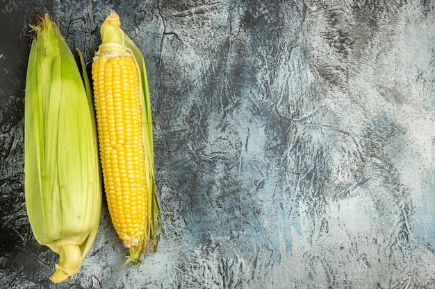 Frische rohe maisgelbpflanze der draufsicht auf grüner fotopflanze des dunklen hellen bodens