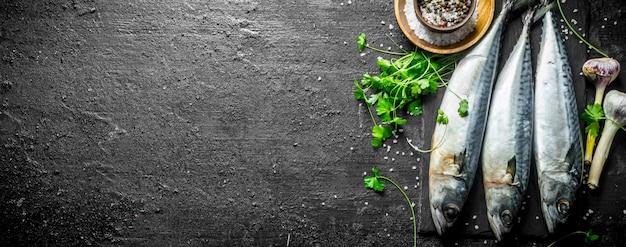 Frische rohe makrele auf einem steinbrett mit knoblauch, gewürzen und kräutern. auf schwarzem rustikalem tisch