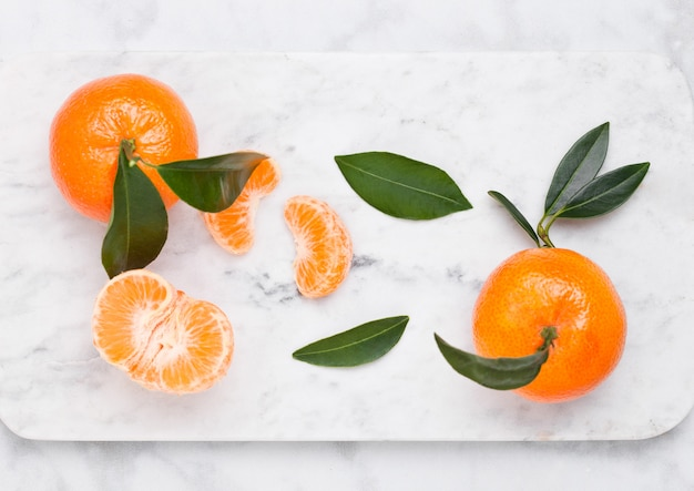 Frische rohe mandarinen tragen mit blättern auf marmorhintergrund früchte