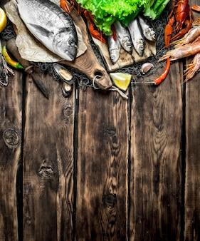 Frische rohe meeresfrüchte. eine vielzahl von meeresfrüchten auf fischernetz auf holztisch.