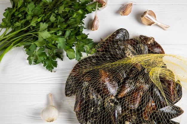 Frische rohe miesmuscheln in einem gitter mit petersilie und knoblauch