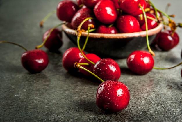 Frische rohe organische saisonfrüchte. kirsche mit wassertropfen auf einer dunklen steintabelle. copyspace