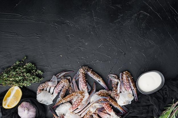 Frische rohe pferdekrabbe, blaue krabbe, blumenkrabbensatz, auf schwarzem hintergrund, draufsicht flache lage, mit copyspace und platz für text