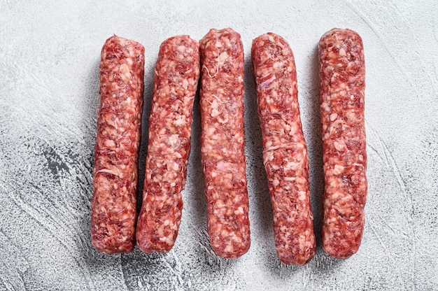Frische rohe rindfleischfleisch kebabs würstchen. weißer hintergrund. draufsicht.