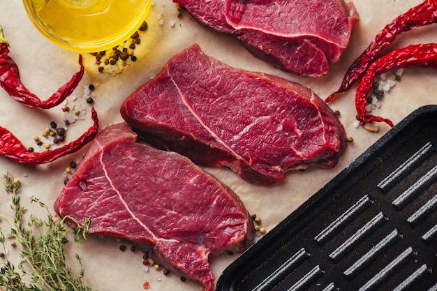 Frische rohe rindfleischfleischsteakscheiben mit den gewürzen und olivenöl bereit zum kochen