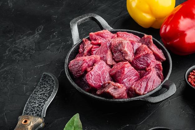 Frische rohe rindfleischwürfel mit süßem paprika in einer gusseisernen pfanne auf schwarzem stein