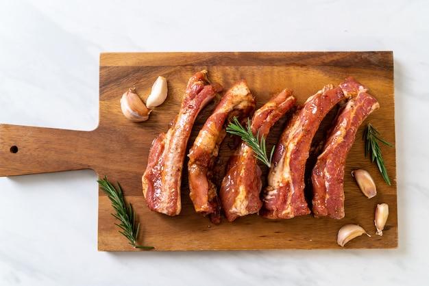 Frische rohe schweinefleischrippen bereit zum braten mit bestandteilen