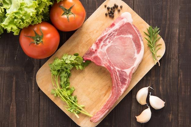 Frische rohe schweinekoteletts und gemüse auf holz