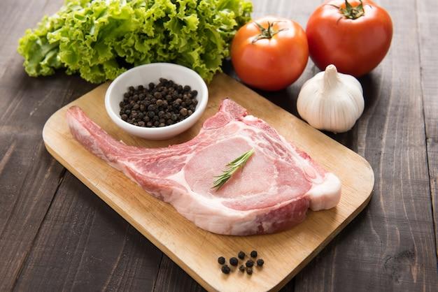 Frische rohe schweinekoteletts und gemüse auf holztisch.