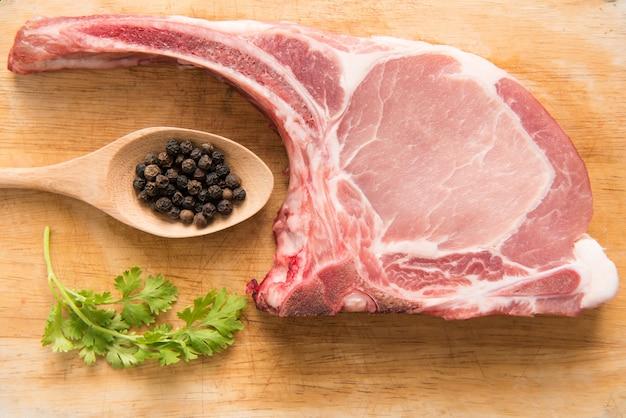 Frische rohe schweinekoteletts und pfeffer im löffel auf holz