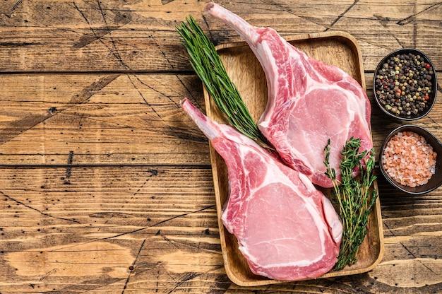 Frische rohe schweinelendenkoteletts mit pfeffer und salz. hölzerner hintergrund