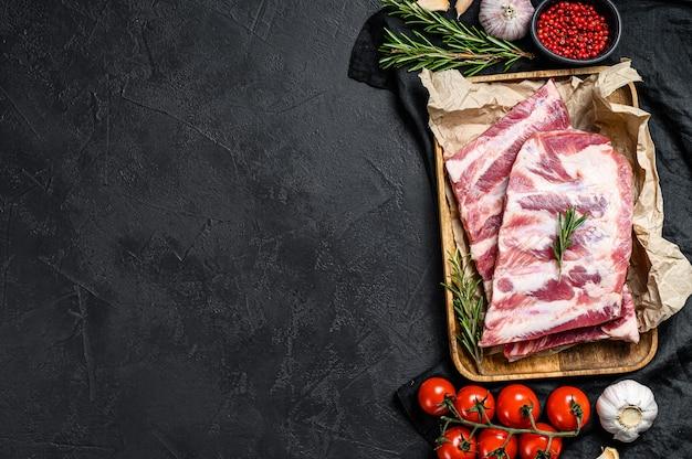 Frische rohe schweinerippchen mit rosmarin und knoblauch in einer holzschale. schwarzer hintergrund. draufsicht. platz für text
