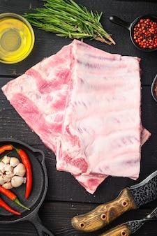 Frische rohe schweinerippchen mit rosmarin und knoblauch, mit grillmesser und fleischgabel, auf schwarzem holztisch, draufsicht flach gelegt