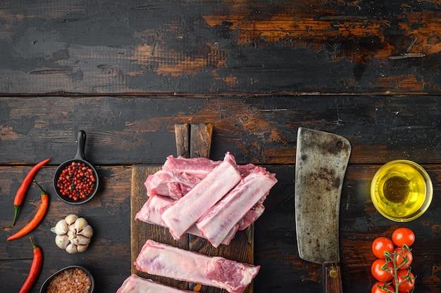 Frische rohe schweinerippchen mit rosmarin und knoblauch, mit honig, mit altem fleischbeilmesser, auf altem dunklem holztisch, draufsicht flach gelegt