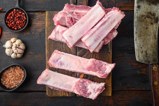 Frische rohe schweinerippchen mit zutaten, mit altem fleischbeilmesser, auf altem dunklem holztisch, draufsicht flach gelegt