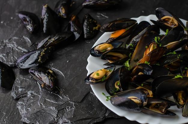 Frische rohe und gekochte miesmuscheln auf schwarzem schieferstein