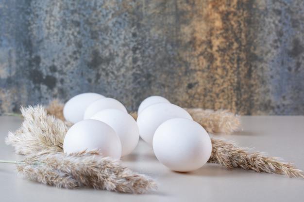 Frische rohe weiße hühnereier auf beige tisch gelegt.