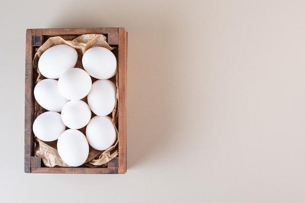 Frische rohe weiße hühnereier in der alten holzkiste.