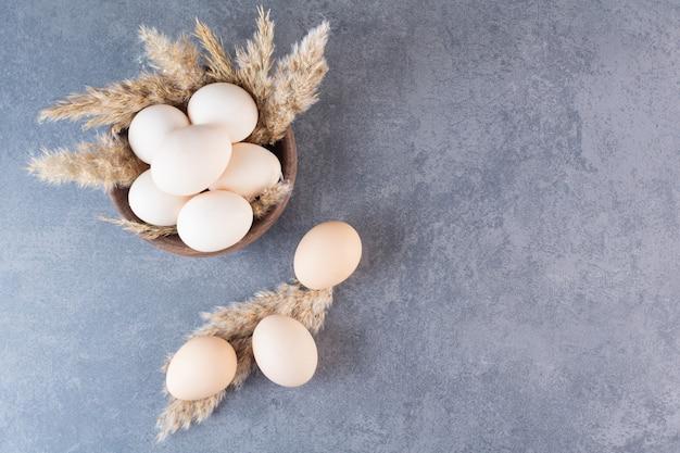 Frische rohe weiße hühnereier in der holzschale.
