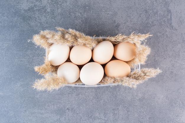 Frische rohe weiße hühnereier mit weizenähren auf steintisch gelegt.
