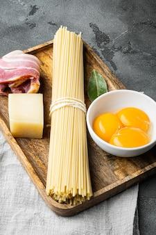 Frische rohstoffe für traditionelle italienische pasta carbonara-set, auf grauem steinhintergrund