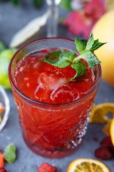 Frische rosa limonade mit himbeeren verziert mit minzblättern, orange, limette und kandierten früchten auf einem dekorativen hintergrund