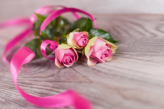 Frische rosa rosen auf holz