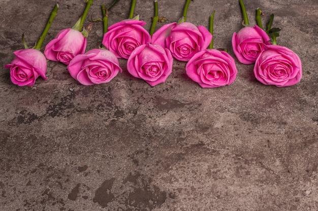 Frische rosa rosen auf strukturiertem steinbetonhintergrund. grußkarte für hochzeiten, geburtstage, 8. märz, muttertag oder valentinstag