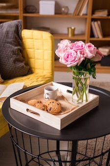 Frische rosa rosen im glas wasser, tasse kaffee, knusprige hausgemachte kekse in holzkiste auf kleinem tisch von gelbem sofa mit kissen