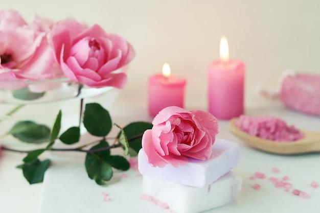 Frische rosa rosen, wasser, blütenblätter, kerzen, körperpflegeprodukte