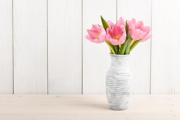 Frische rosa tulpen in einem krug auf holz