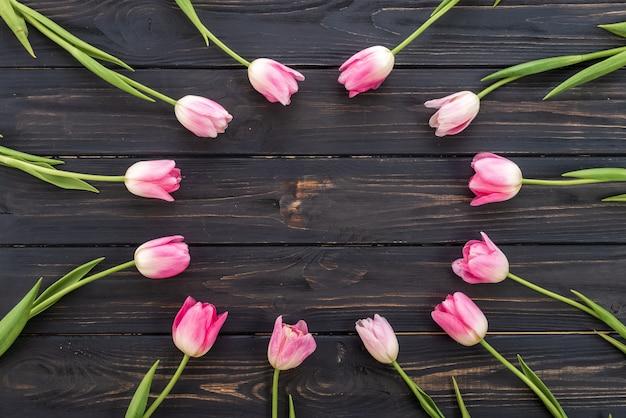 Frische rosa tulpenblumen auf holztisch. draufsicht mit textfreiraum