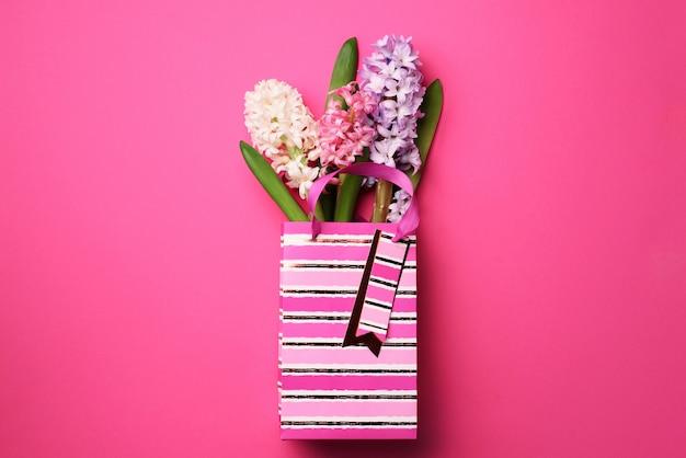 Frische rosa, weiße, violette hyazinthenblumen in der einkaufstasche auf schlagkräftigem pastellhintergrund.