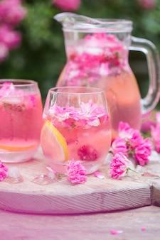Frische rosenlimonade mit eis und frischen rosen über natürlichem garten