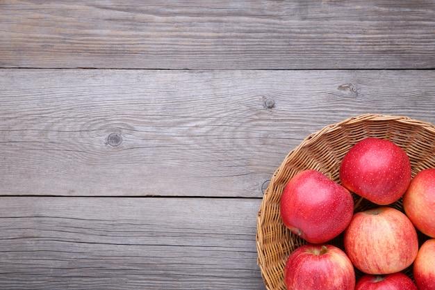 Frische rote äpfel auf hölzernem hintergrund. frische rote äpfel in einem korb