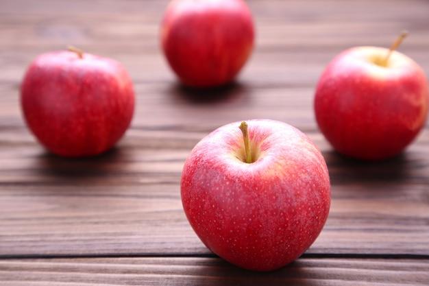 Frische rote äpfel auf hölzernem hintergrund. geschmackvolle äpfel auf brauner tabelle