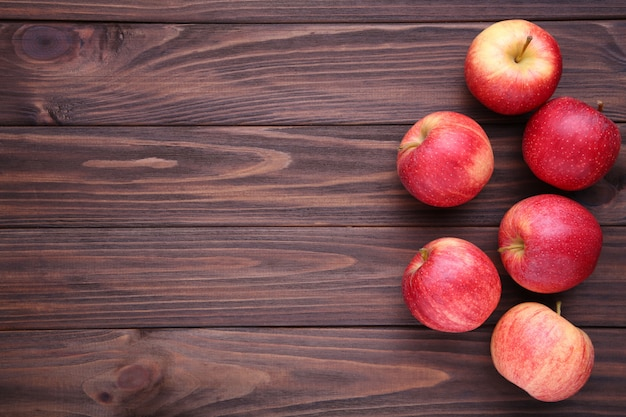 Frische rote äpfel auf hölzernem hintergrund