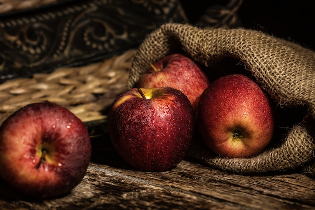 Frische rote äpfel auf hölzerner rustikaler tabelle
