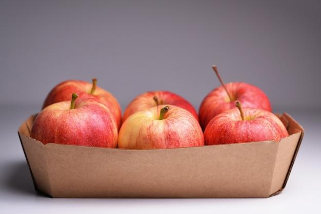 Frische rote äpfel in einem papierbehälter frische rote äpfel im karton auf grauem hintergrund