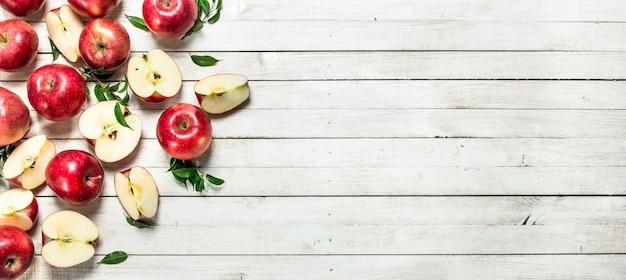 Frische rote äpfel mit blättern. auf einem weißen hölzernen hintergrund.