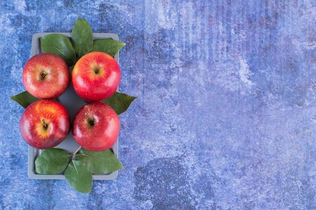 Frische rote äpfel mit blättern auf tablett über blau.