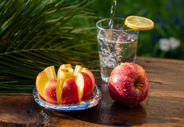 Frische rote äpfel und glas wasser auf einem holztisch am sonnigen tag